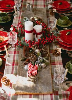 Holiday table scape, candles, pine ones sitting on a plank of aged wood.