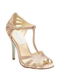 """You'll fall in love with these gorgeous glitter t-strap sandal with cut-out detail! Blue by Betsey Johnson t-strap glitter sandals feature all over cut-out detail. Heel measures 4"""". Available in Ivory, Silver and Champagne. Fully lined. Imported."""