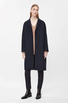 This single-breasted coat is made from wool with a lightly textured finish and soft cotton lining. Slightly oversized, it has full-length kimono sleeves, notched lapels and two welt pockets on the front. It is secured with a tonal button fastening.