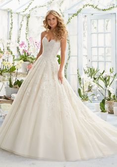 Pearl and Crystal Beading on elegant Embroidery that decorates the classic Tulle ball Wedding Dress. Colors:White, Ivory and Champagne.