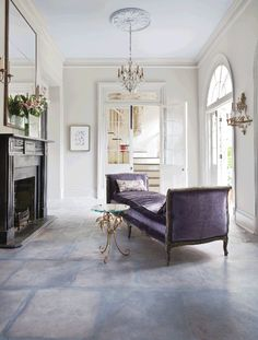 The 19th-century daybed was reupholstered in purple velvet. The gilded side table is from Source.