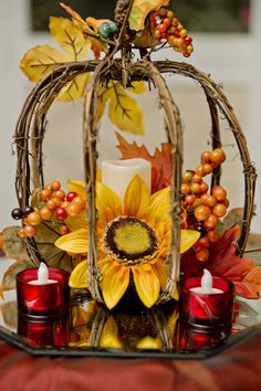 "Create a ""cage"" out of twigs, and decorate it with flowers, berries, and candles."