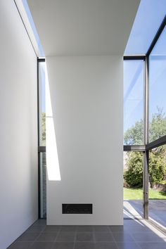 Narrow slices of glazing break up the plain white facade of this residential extension