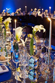 Long banquet tables are covered in mirrored linens and punctuated with a mix of white calla lilies and taper candles.