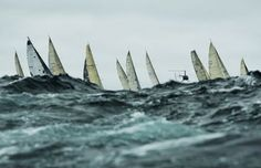 This shot captures yachts battling wild swell outside the Sydney Heads as the fleet sails out of Sydney Harbour down the East coast of Australia. The masts and sails are the only parts of the yachts visible as they drop down behind swell in the foreground. I was positioned hanging out the back of a media boat that was rolling around in the swell as we made our way over waves in the heavy conditions. The sails appear like fins protruding out of the rough ocean.  I have covered many…