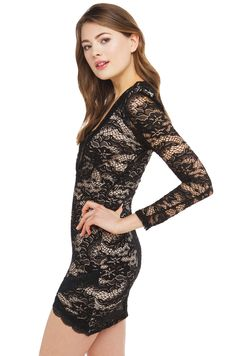 Lace Dress in black- features black lace overlay, nude lining, deep v-neckline, long sleeves, hidden zipper, shoulder pads, and overlapping hemline. Free standard shipping U.S +$75.