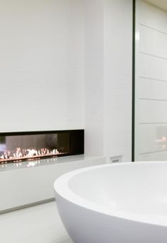 Glossy white bathroom combined with minimal fireplace, Private House Chameleon in Mallorca _