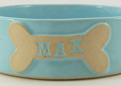 This custom made dog bowl is hand made and finished with your dogs name stamped and glazed individually onto a dog bone. Each of these is formed entirely by hand and is a unique item for that special furry someone!  All my pieces are stoneware pottery and glazed in food safe glazes. As with any hand built item there will be some variation in size between pieces, which is part of their charm, so all dimensions are as accurate as possible. Although technically dishwasher safe I would recommend…