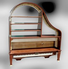 Here are a series of photos showing the transformation of an old Baby Grand Piano into an entertainment shelf/bookcase. This is no small project! Incredible workmanship, and a truly stunning piece of furniture.