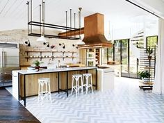 "Renovation: Justin Hemmes transforms his family's historic waterfront mansion: He was keen to preserve some of the memories of the past. ""There was a very communal, social feeling at the house,"" he recalls about his childhood at The Hermitage.   Carrara marble, copper fittings and pale European oak joinery reflect the natural light in the spacious open kitchen. The bell-jar pendant lights are from Le Forge."
