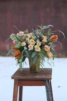 Centerpiece with orange tulips, Chablis spray roses, peach stock, seeded eucalyptus, willow eucalyptus, blue star fern, Kalanchoe tomentosa, Echeveria lilacina and dusty miller, by Floral Verde LLC in Cincinnati, OH.