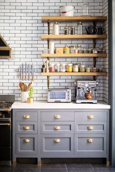 Blue-gray kitchen counters with copper hardware, classic white subway tiles, butcher block countertops, open shelving, and marble accents