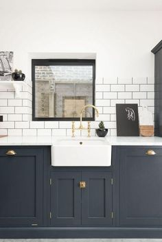 Sink run and upper and lower kitchen cabinets painted in Pantry Blue with aged brass Ionian faucet fixtures and drawer pull hardware, pairs beautifully with traditional subway tiles in white on top of dark gray grout for easy cleaning and maintenance.