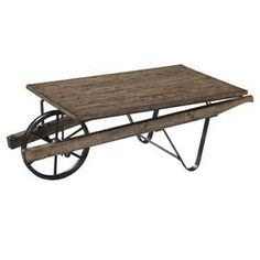 Farm cart-shaped coffee table with a natural finish and slatted pine top.  Product: Coffee tableConstruction Material: Pine veneer, metal and hardwood solidsColor: Pine Features:  Country styleFarm cart style Dimensions: 19 H x 56 W x 28 D