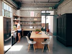 Great industrial kitchen with concrete floors and walls, mullioned windows, wood cabinets and open shelves