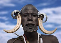 Mursi woman tribe with hippo tusks - Omo valley Ethiopia