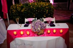 Sweetheart table with a hydrangea and lime centerpiece and fuchsia runner lined with candles. Don't forget the Mr. & Mrs. signs!