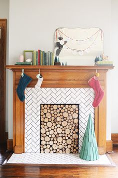 This faux stacked log fireplace insert was made by simply cutting up backyard branches and gluing them onto a piece of plywood painted black. Chelsea Mohrman of Farm Fresh Therapy has more about it, and her living room decoarated for Christmas, on The Home Depot Blog. || @chelseamohrman