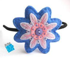 Tiara com flor em feltro bordado, com aplicação de botão e contas. Dimensões: 8,0 cm de diâmetro. Fino acabamento...