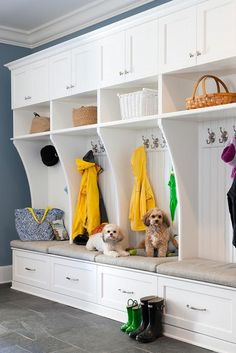 White and blue mudroom features white mudroom lockers accented with beadboard trim, one locker for each family member, fitted with closed cabinets, shelves and bench drawers.