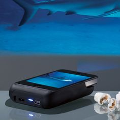 projects movies on the wall.... this is super cool Pocket Projector for iPhone® 4 and 4S Devices