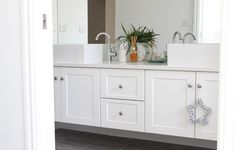 "Katrina Lee Chambers blog: floating bathroom vanities with door profile to match kitchen. Mirrors go all the way to ceiling, bench is Caesarstone ""Osprey""."