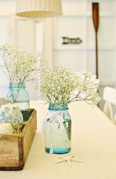 Small jars and simple flowers, like baby's breath in wooden tray.