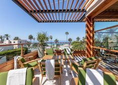 elephante patio green seats with a nod to boomerang retro gives a rustic meets modern vibe to this dining area lanai. Rooftop Restaurant, Ocean Views, Lanai, Interior S, Trade Show, Rustic Modern, Santa Monica, Dining Area, Oasis