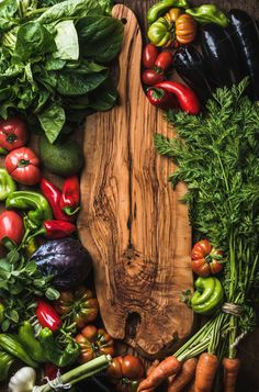 #Fresh raw vegetable ingredients Fresh raw vegetable ingredients for healthy cooking or salad making on wooden background with rustic wooden board in center top view copy space vertical composition. (Top View Food)