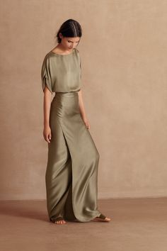 Laurel, long party dress made in aloe green martellato silk satin sourced from Italy. The body of the dress is loose fitted and has short drop shouldered rolled sleeves. The skirt of the dress is like a pareo and is tied at the waist. This heavy silk moves beautifully as you walk. Shop online at www.cortana.es/en