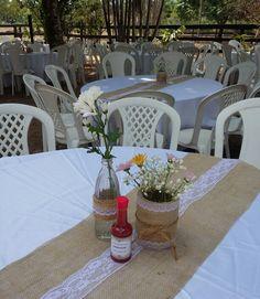 Centros d e mesa com latas forradas com juta e renda, garrafinhas e Pimenta para apimentar o dia.