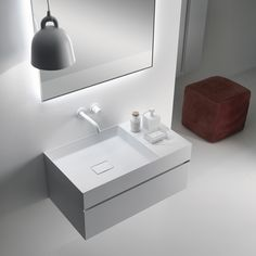 The importance of details. QUATTRO.ZERO h 24 cm single drawer furniture unit with grooved handle, new washbasin in Ceramilux SSL with 25 cm side shelf and door columns, in matt White lacquered finish. Discover more on www.falper.it