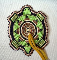 This listing is for one beaded turtle magnet. Beadwork done on turtle is flat beading. Made with size 11 seed beads, cut beads, tin cones, deer