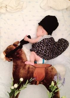 sleeping baby riding her horse