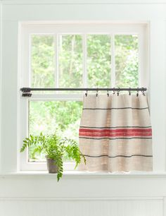 No sewing required to make this cafe curtain! Use a seam ripper to remove the stitching from a grain sack. Unfold and trim to fit the measurements of window.