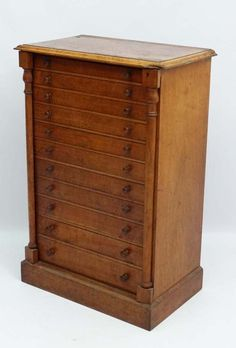 A mid 19thC golden oak Wellington Chest / collectors cabinet comprising 11 graduated drawers. 36 1/4'' high x 24'' wide.