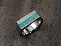 This titanium signet ring with a solid piece of genuine turquoise stone inlay has a substantial presence to it, yet because of the way it has been