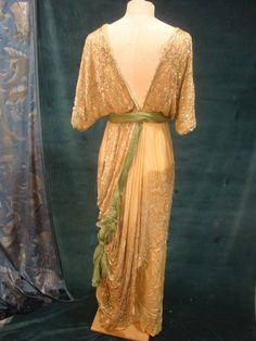 Evening Gown, about 1912 Satin pale yellow silk covered with yellow diaphanous chiffon plenty embroidered salmon on Batwing iridescent tubular beads and rhinestones, beaded apron poppies decorated in pink waves and silver cummerbund green chiffon falling on train (fragile but beautiful state) HOME NEWSLETTER ALERT SUBJECT CONTACT