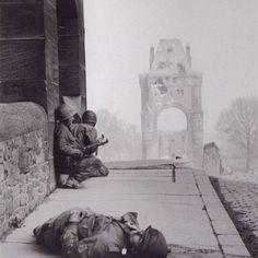 Dois soldados norte-americanos se escondendo logo após um de seus colegas ser atingindo na cabeça por um franco-atirador nazista, Alemanha, 1945.