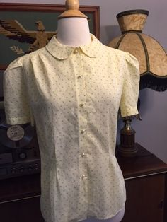 Vintage yellow peter pan collared button up blouse with little pearl bubble buttons. Size: Not marked but fits like a medium  Measurements laying flat  armpit to armpit:18 shoulder:16 total length:25   ❉ All items are vintage and have been worn, some may have small flaws and possibly go unnoticed. I will do my very best to include details of garment accurately.  ALL SALES FINAL! Please contact me for additional questions or details about item.