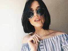 idée de coupe courte femme, carré court classique sur des cheveux couleur noire, lunettes de soleil rondes, tenue été