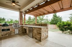 Outdoor kitchen with a built-in green egg, grill, fridge, and bar