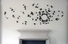 Butterfly shapes cut from soda cans. Shaped to be 3D, painted black, glued to wire (opt.) and attached to wall. Cheap, but time intensive....