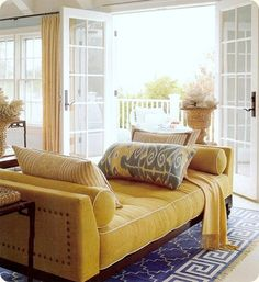 Love the yellow daybed against the bold navy and white rug.