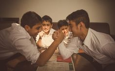 Family and Lifestyle photography - young and playful; the two elder brothers of the family engaged in an arm-wrestling challenge on a beautiful sunny Monday morning while the other two cheers for them.
