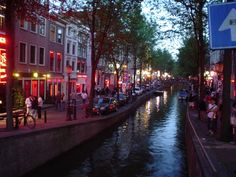 De Wallen is the largest and best known red-light district in Amsterdam and a major tourist attraction. It is located in the heart of the oldest part of the city, covering several blocks south of the church Oude Kerk and crossed by several canals. De Wallen consists of a network of alleys containing approximately three hundred tiny one-room cabins rented by prostitutes who offer their sexual services from behind a window or glass door, typically illuminated with red lights.