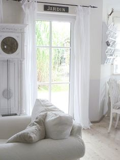 White and Shabby.  Love her garden sign above the curtains she has raised higher than normal.