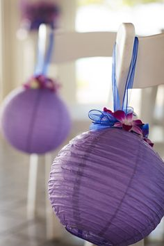 For Tara and Morgan's wedding, we used purple paper lanterns, placed purple orchid flowers in them, and hung them on the aisle chairs using blue ribbon. Photo by Alyssapix. Wedding planned by Tori Rogers of Hawaii Weddings by Tori Rogers www.hawaiianweddings.net. Wedding took place at the Turtle Bay Resort Pavilion.