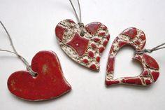 Set: 3 rote Herzen aus Keramik mit Bastbändchen.  2 der Herzen sind mit einem Muster versehen, die Zwischenräume sind mit Oxid eingefärbt, die erhabenen Stellen sind mit roter Glasur versehen....