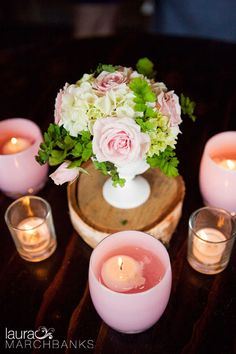 Pink glassybaby votives surround pink and white centerpieces.  Seattle Wedding Photographer Laura Marchbanks Photography photographs a pink wedding at Hidden Meadows in Snohomish, outside Seattle. Bride and groom portraits in downtown Snohomish. Hidden Meadows barn reception featuring pink and green wedding colors.
